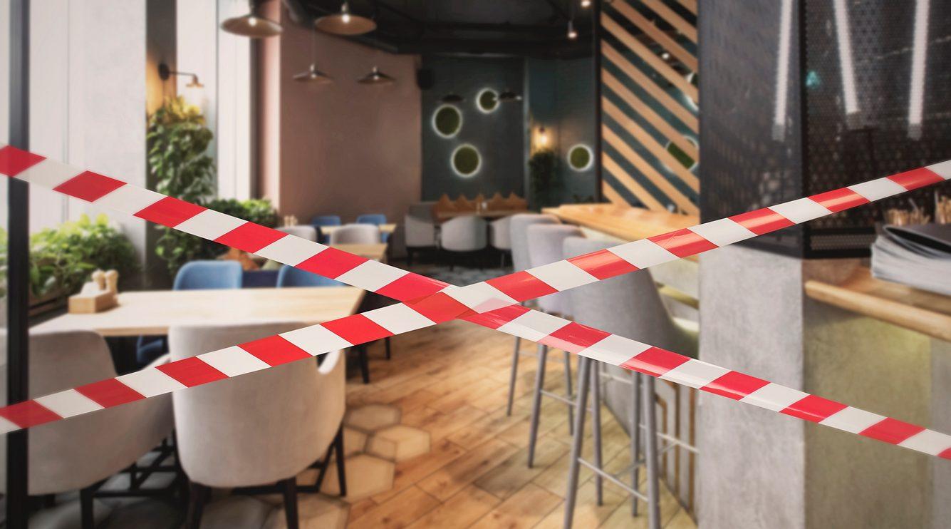 Der Sitzbereich eines Cafés ist mit Flatterband abgesperrt worden.