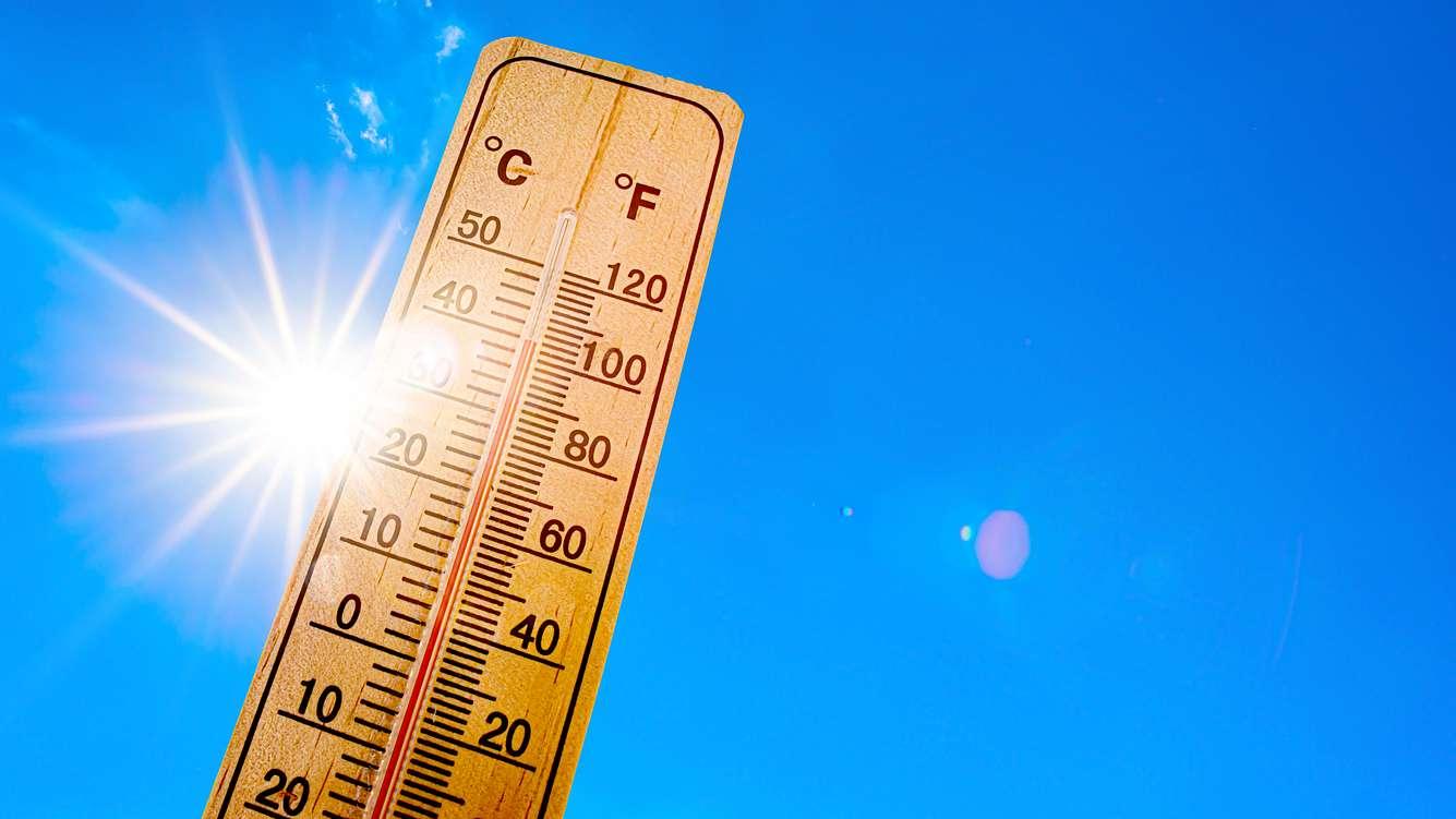 Ein Holzthermometer vor blauem Himmel mit Sonnenschein.