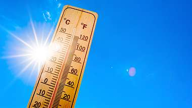 Ein Holzthermometer vor blauem Himmel mit Sonnenschein.  - Foto: iStock / Xurzon