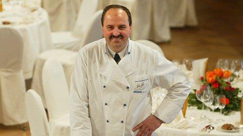Johann Lafer steht vor einem gedeckten Tisch. - Foto: Ralph Orlowski / Freier Fotograf