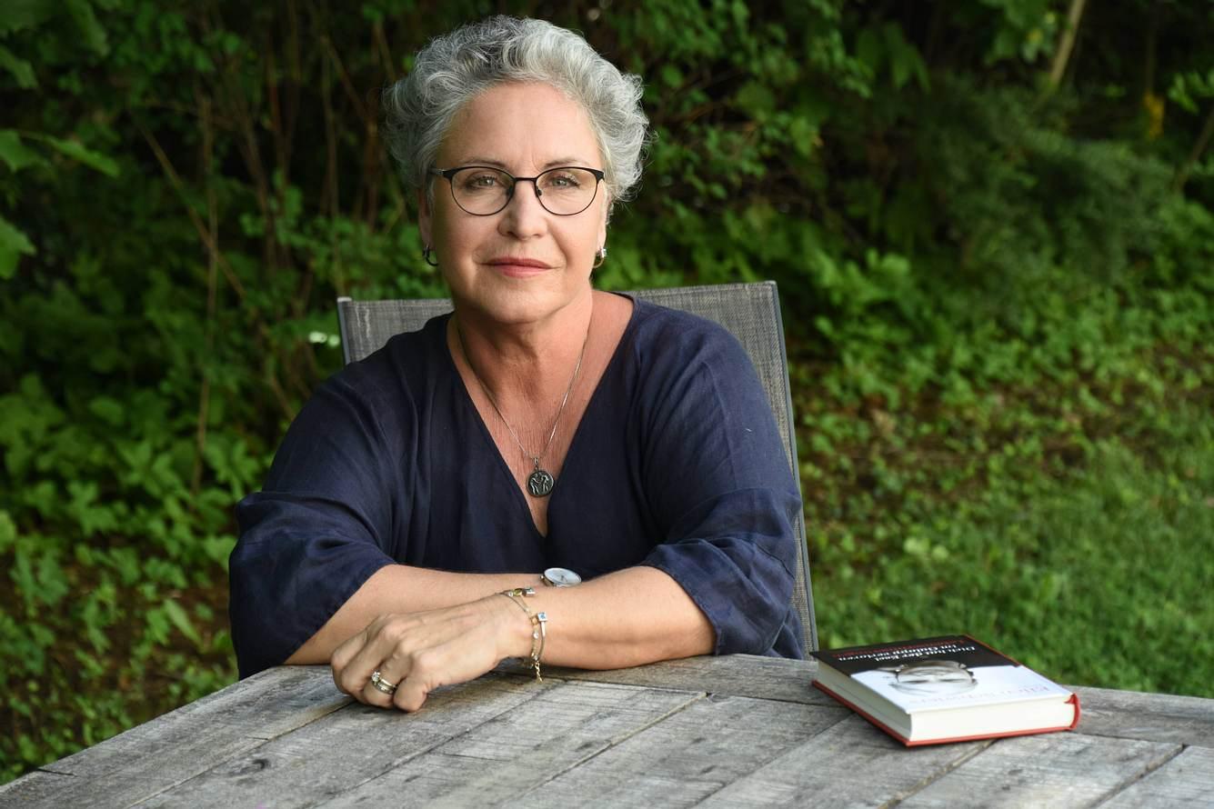 Schauspielerin Katerina Jacob mit ihrem Buch an einem Gartentisch.