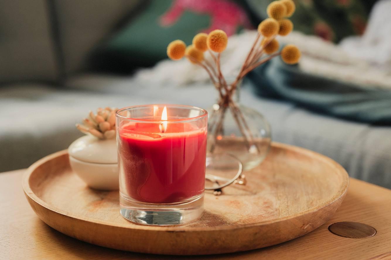 Rote Kerze im Glas steht auf einem Holztablett