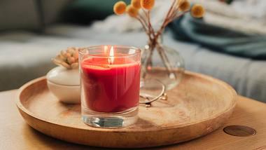 Rote Kerze im Glas auf einem Holztablett - Foto: iStock/knape