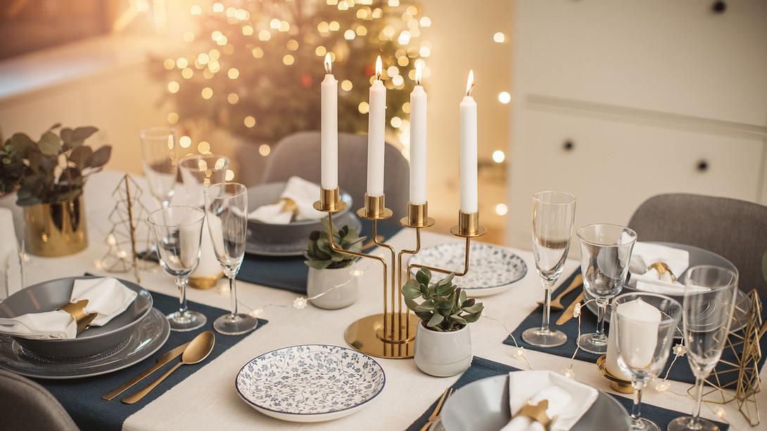 Goldener Kerzenständer auf gedeckter Tafel - Foto: iStock/svetikd