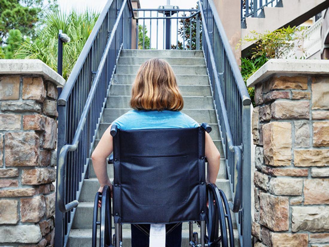 Busfahrer baut Rampe für Mutter mit Kind im Rollstuhl.