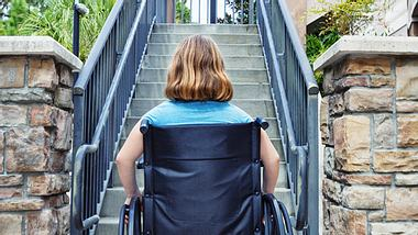 Busfahrer baut Rampe für Mutter mit Kind im Rollstuhl.  - Foto: Powerofforever / iStock