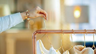 Frau hängt Kleiderbügel an Kleiderständer - Foto: iStock/CentralITAlliance
