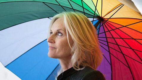 Frau schützt sich mit Regenschirm vor krausen Haar