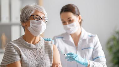 Eine ältere Dame mit Mundschutz wird geimpft. - Foto: iStock / Choreograph