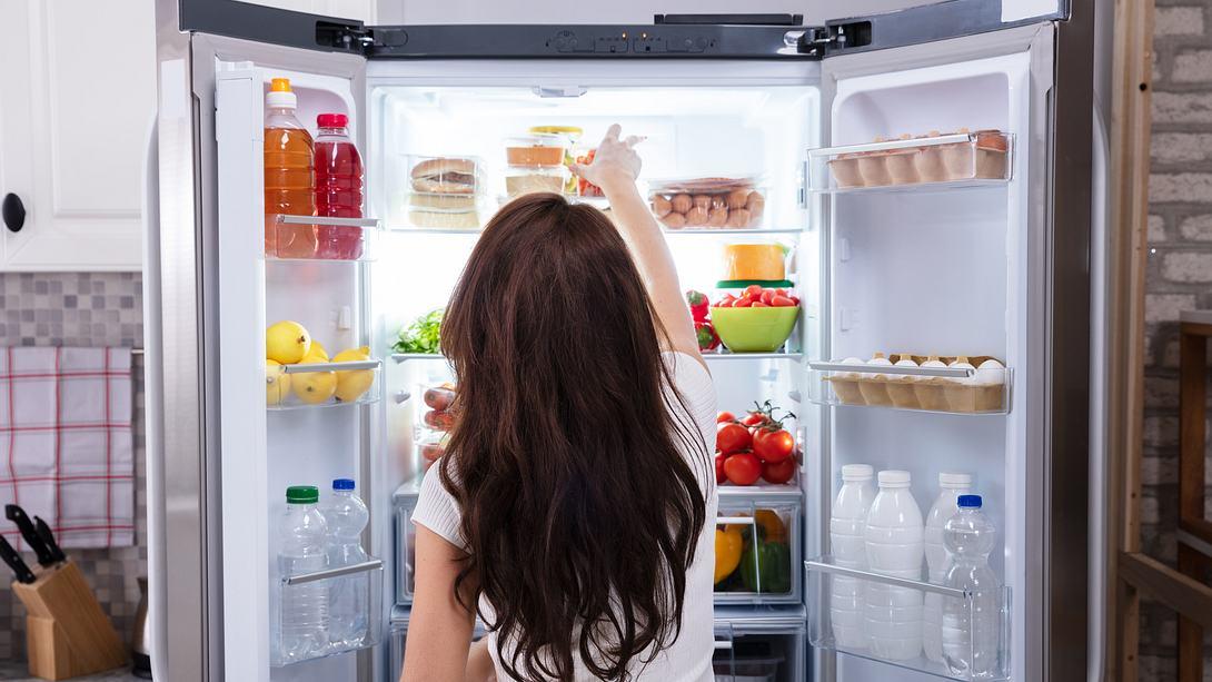 Frau steht vor dem Kühlschrank und greift nach einem Kühlschrank-Organizer - Foto: iStock/AndreyPopov
