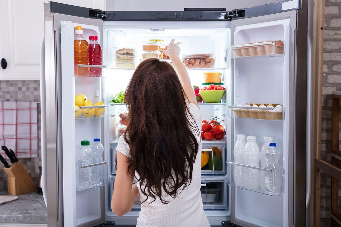 Frau steht vor dem Kühlschrank und greift nach einem Kühlschrank-Organizer
