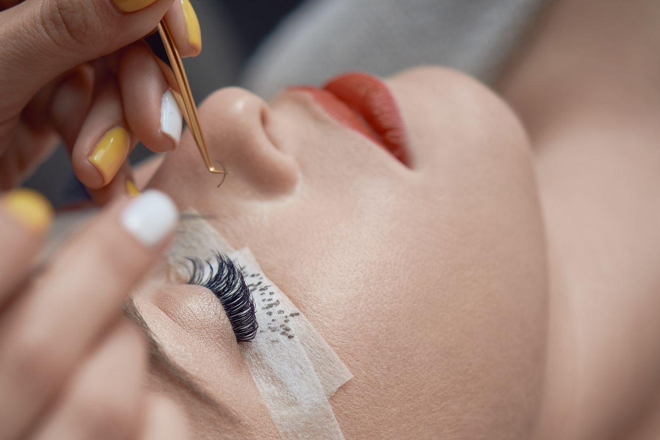 Kosmetikerin klebt künstliche Wimpern bei anderer Frau mit geschlossenen Augen an.