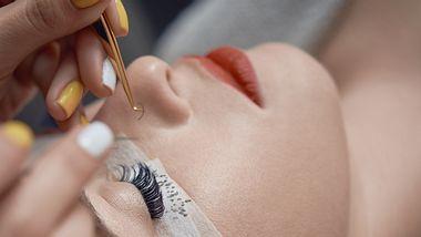 Kosmetikerin klebt künstliche Wimpern bei anderer Frau mit geschlossenen Augen an. - Foto: iStocke/stock_colors