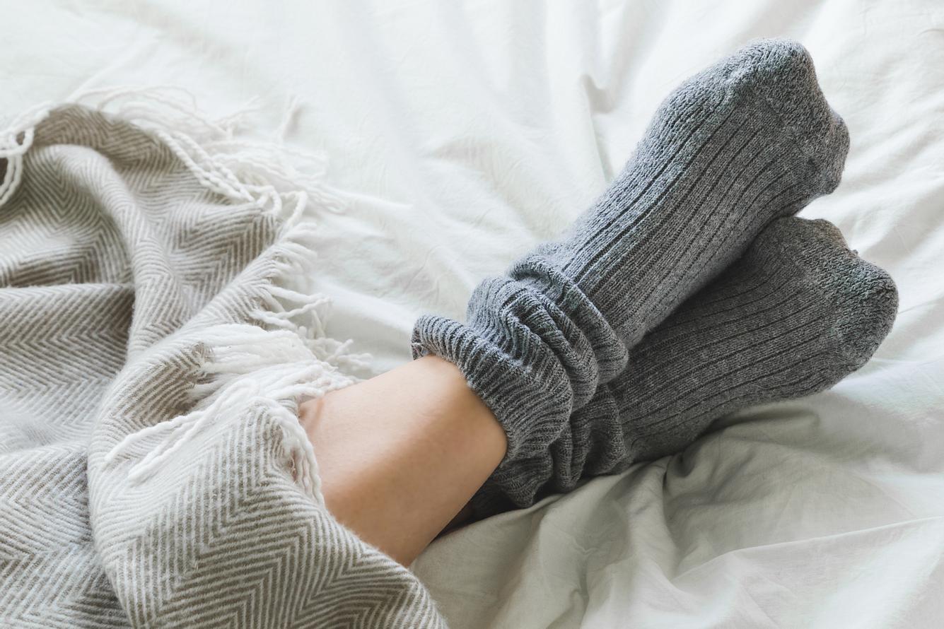 Graue Kuschelsocken auf weißem Bettlacken