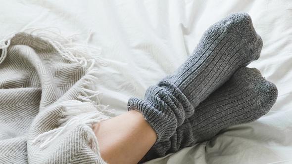 Graue Kuschelsocken auf weißem Bettlacken - Foto: iStock/locknloadlabrador