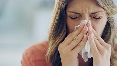 Eine Frau putzt sich die Nase. - Foto: iStock / Cecilie_Arcurs