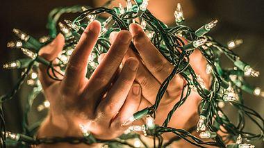 Es gibt verschiedene Möglichkeiten, Lichterketten am Weihnachtsbaum anzubringen. - Foto: kenlh / iStock