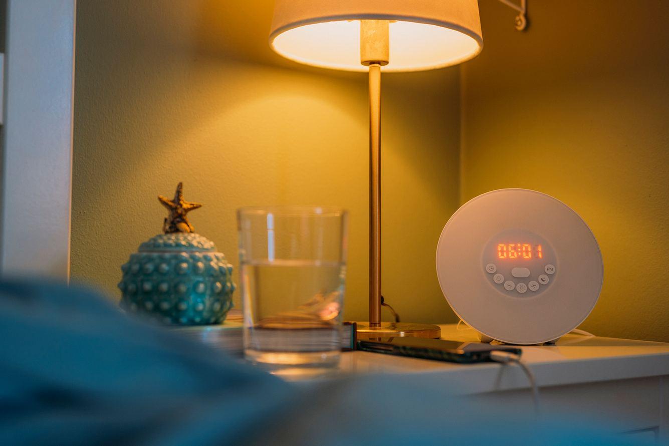 Ein Lichtwecker steht in einem Schlafzimmer auf dem Nachttisch.