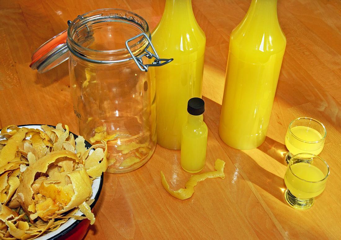 Selbstgemachter Limoncello aus Zitronenschalen auf einem Tisch.