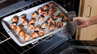 Maronen auf einem Backblech werden im Backofen geröstet. - Foto: patrickheagney / iStock