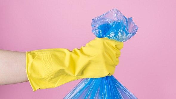 Hand hält Müllbeutel - Foto: iStock/InspirationGP