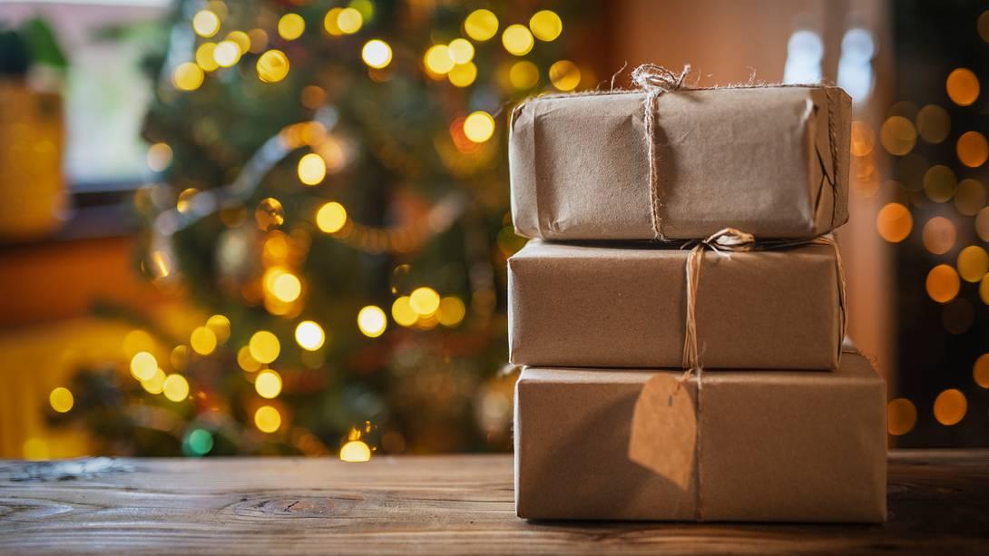 Nachhaltige Geschenke liegen eingepackt auf einem Holztisch - Foto: iStock/ArtistGNDphotography