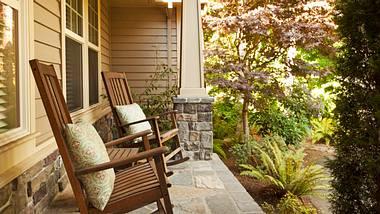 Outdoor Schaukelstuhl auf einer Veranda. - Foto: iStock/ chuckcollier