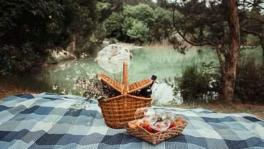 Decke und Korb, gefüllt mit leckeren Picknick-Rezepten, in der Natur - Foto: iStock/Vikhristyuk Sergey