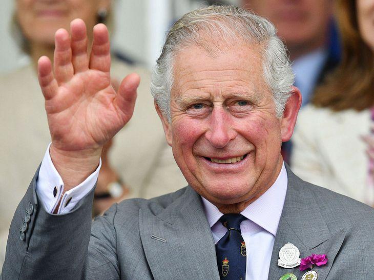 Prinz Charles winkt und lacht in die Kamera