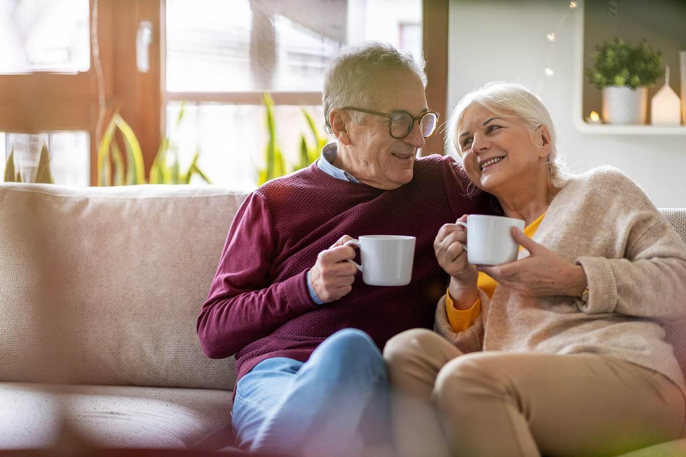 Ein älteres Ehepaar hat es sich mit Kaffeetassen auf der Couch gemütlich gemacht.