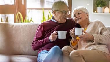 Ein älteres Ehepaar hat es sich mit Kaffeetassen auf der Couch gemütlich gemacht. - Foto: iStock / Piksel