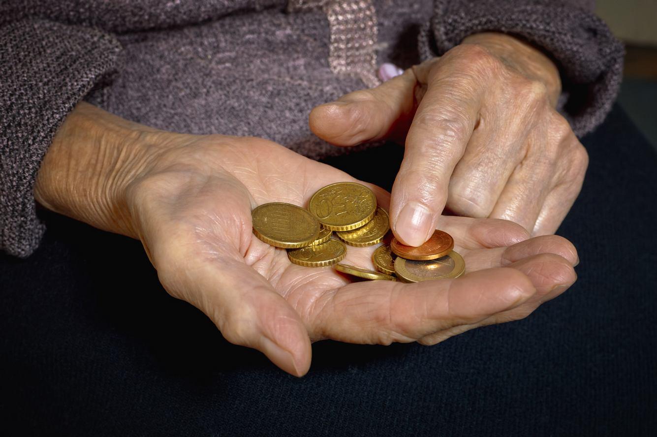 Frau zählt münzen in ihrer Hand.