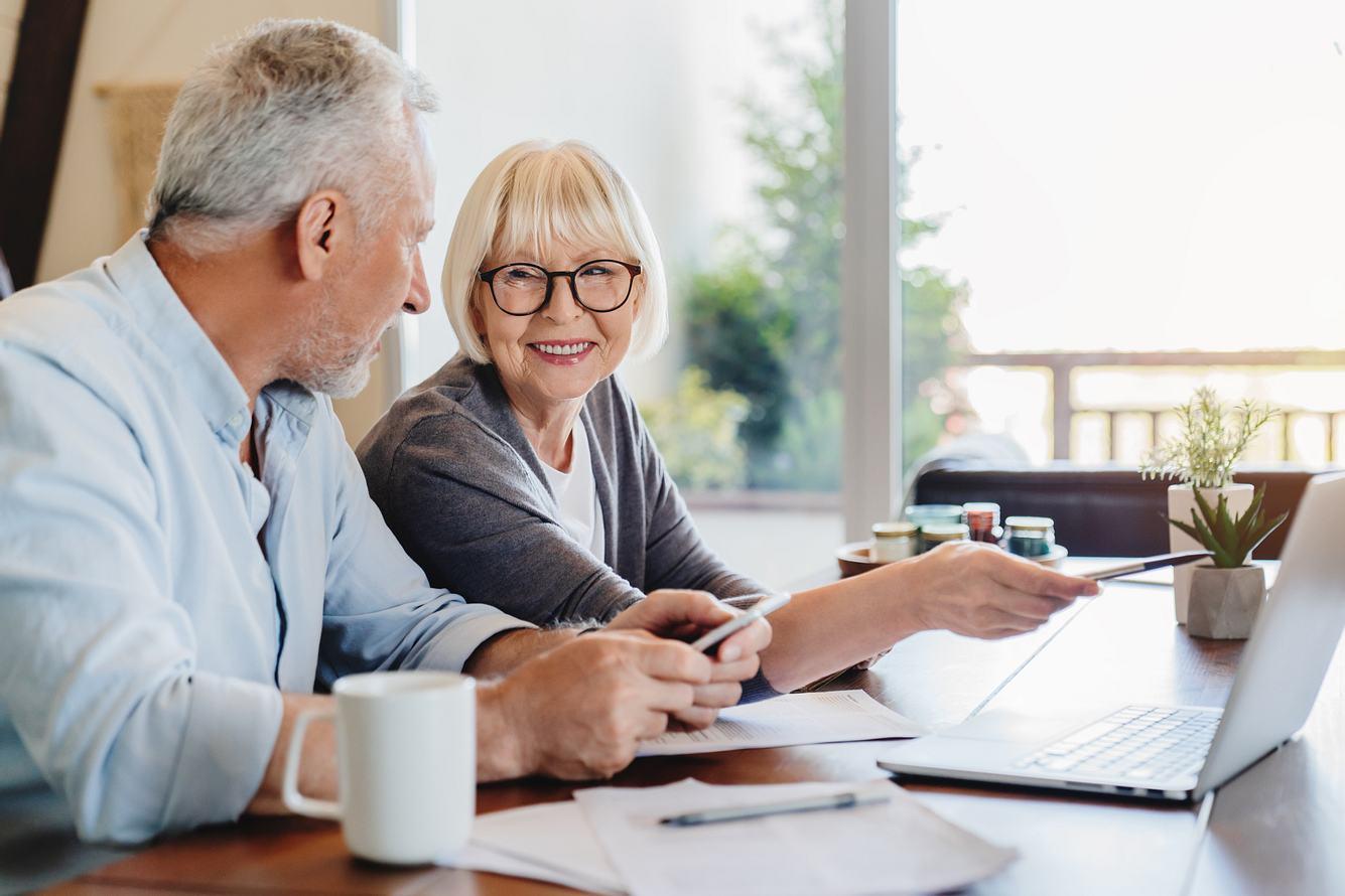 Zwei Senioren sitzen mit Anträgen vor dem Computer.