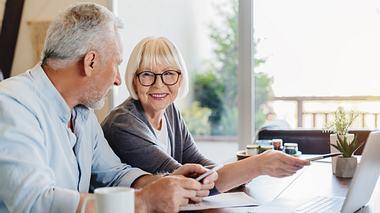 Zwei Senioren sitzen mit Anträgen vor dem Computer.  - Foto: iStock / Inside Creative House