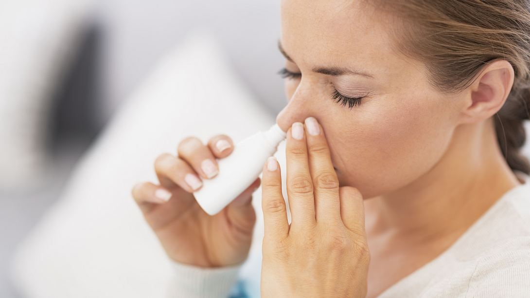 Eine Frau benutzt Nasenspray. - Foto: iStock / CentralITAlliance