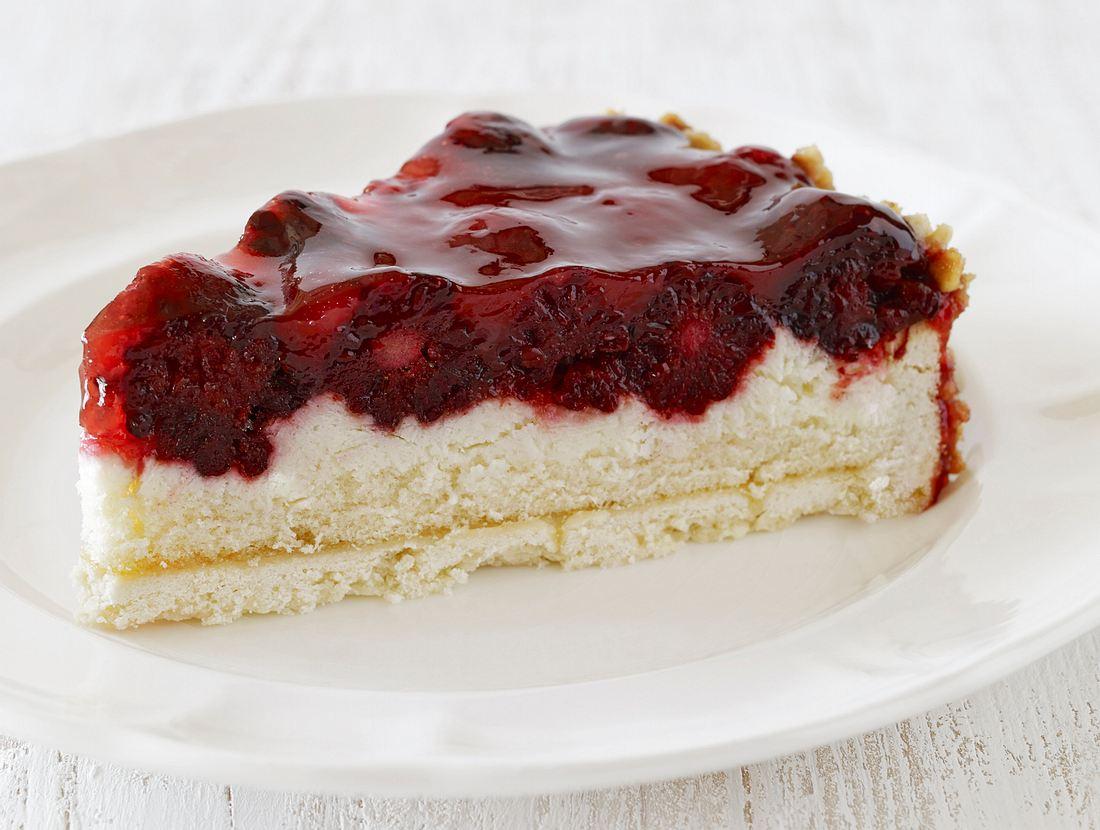 Ein Stück Rote-Grütze-Kuchen auf einem weißen Teller.