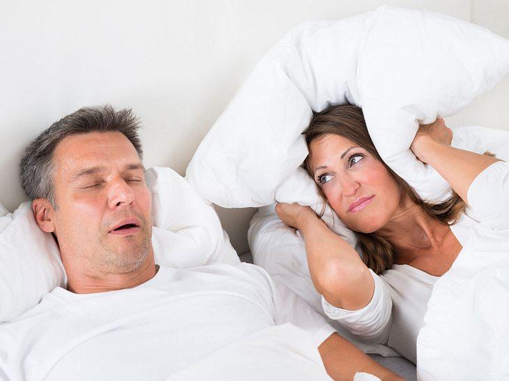 Paar liegt im Bett, Mann schnarcht und hat Atemaussetzer, Frau hält sich die Ohren zu.