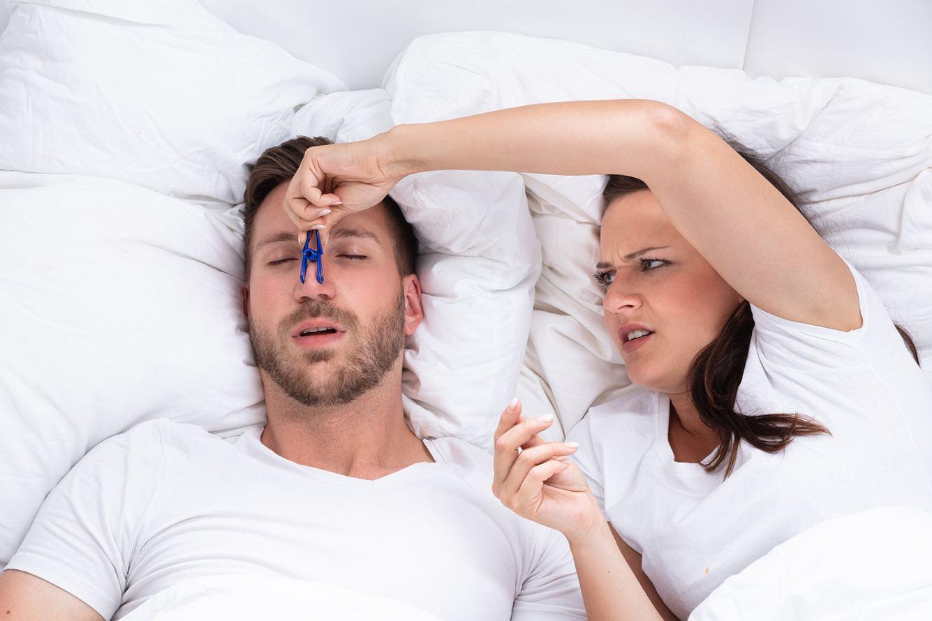 Ein Mann schläft schnarchend neben seiner Frau im Bett