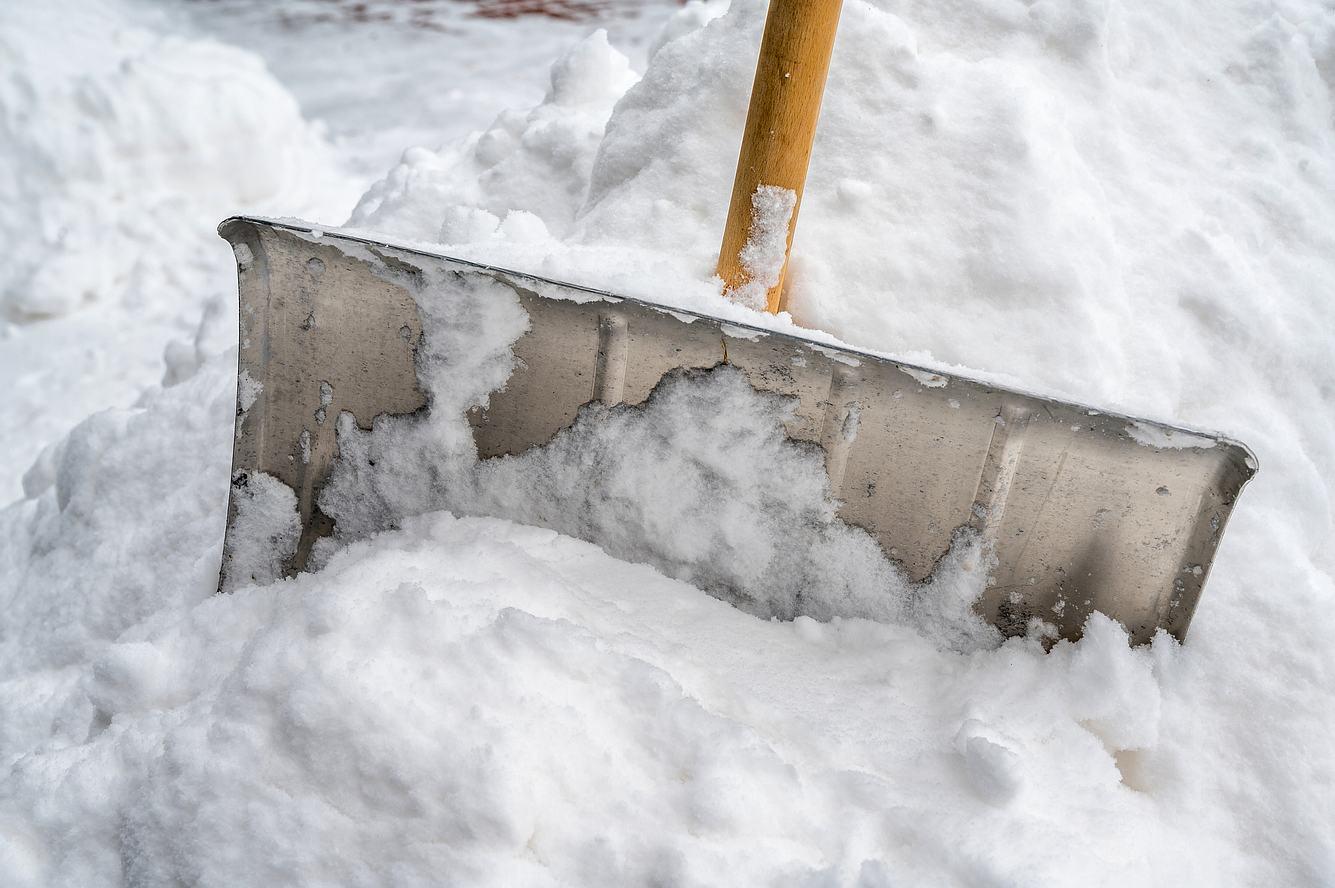 Schneeschieber aus Metall bei der Arbeit