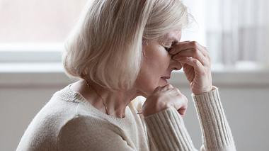 Eine Frau mittleren Alters leidet an Kopfschmerzen - Foto: fizkes / iStock