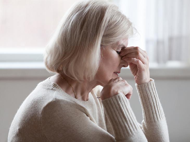 Eine Frau mittleren Alters leidet an Kopfschmerzen