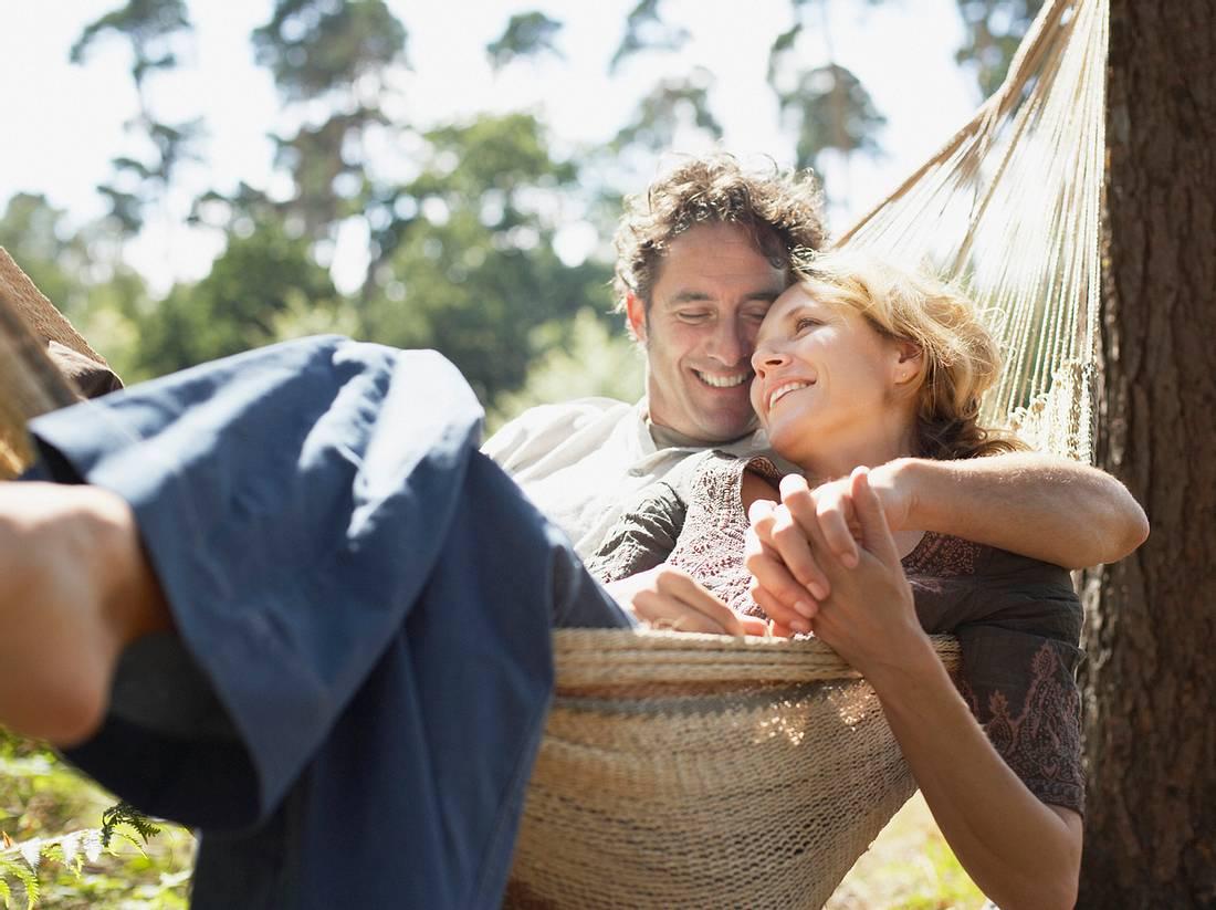 Ein Mann und eine Frau liegen kuschelnd in einer Hängematte