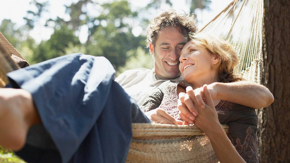 Ein Mann und eine Frau liegen kuschelnd in einer Hängematte - Foto: Paul Bradbury / iStock