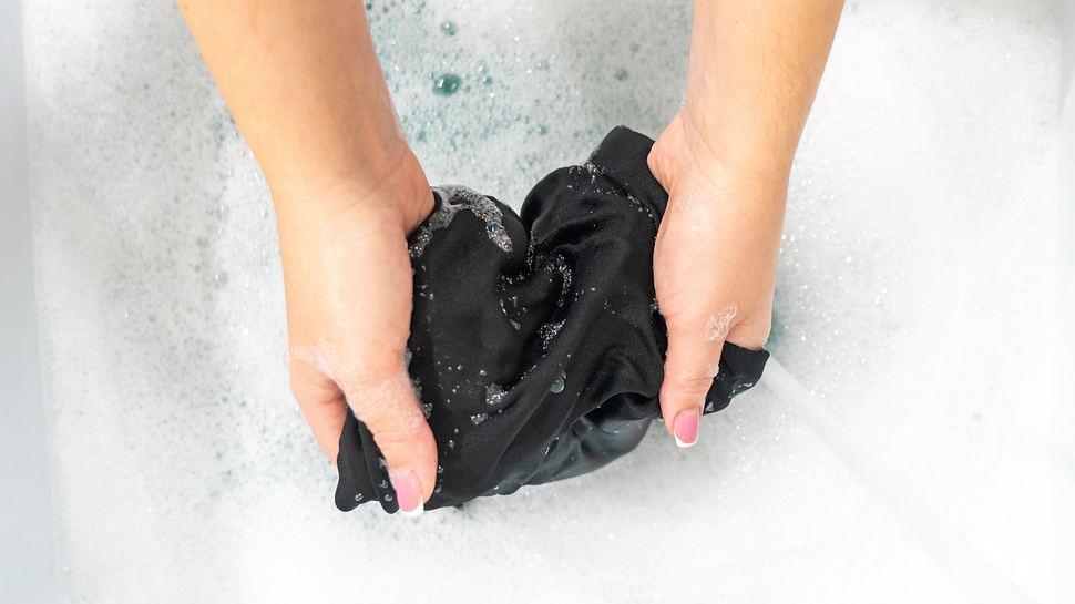 Ein schwarzes Stück Seide wird im Schaumbad gereinigt. - Foto: iStock / Mariakray