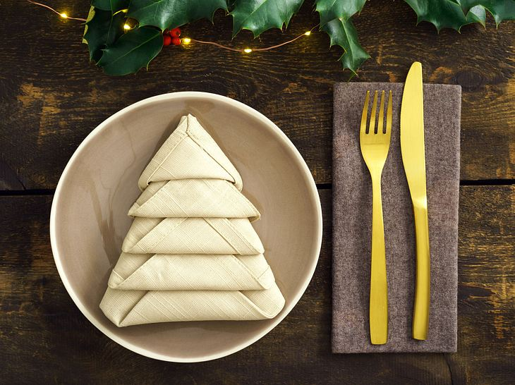 Wenn Sie Ihre Serviette so falten wie hier gezeigt, dann sieht sie aus wie ein Tannenbaum.