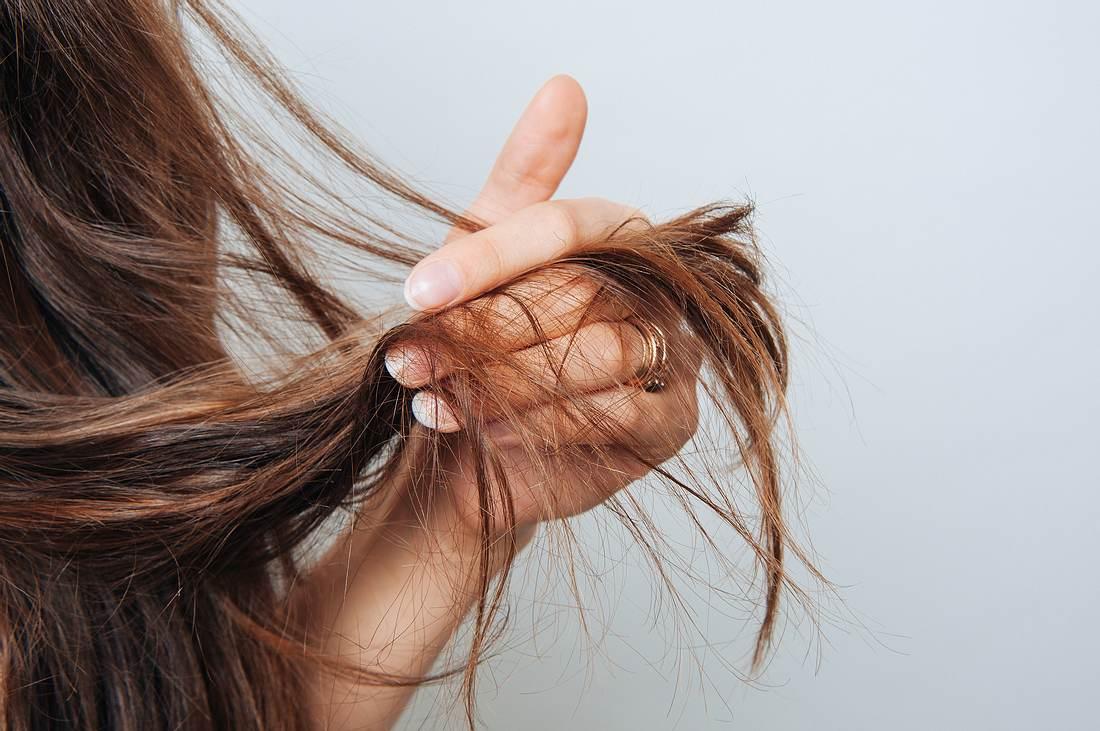 Frau hat trockenes Haar in der Hand