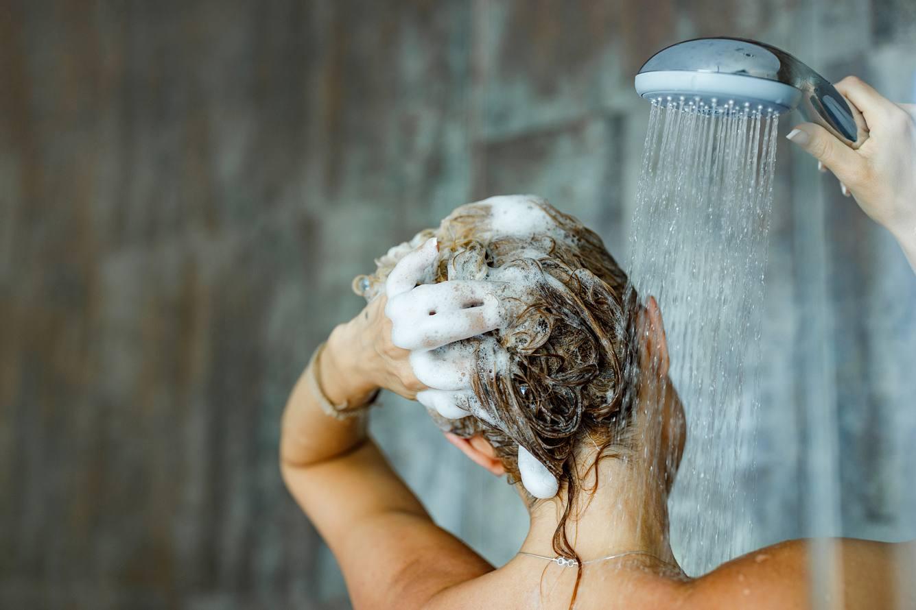 Frau wäscht sich die Haare mit Shampoo.
