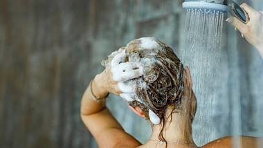 Frau wäscht sich die Haare mit Shampoo. - Foto: iStock/skynesher