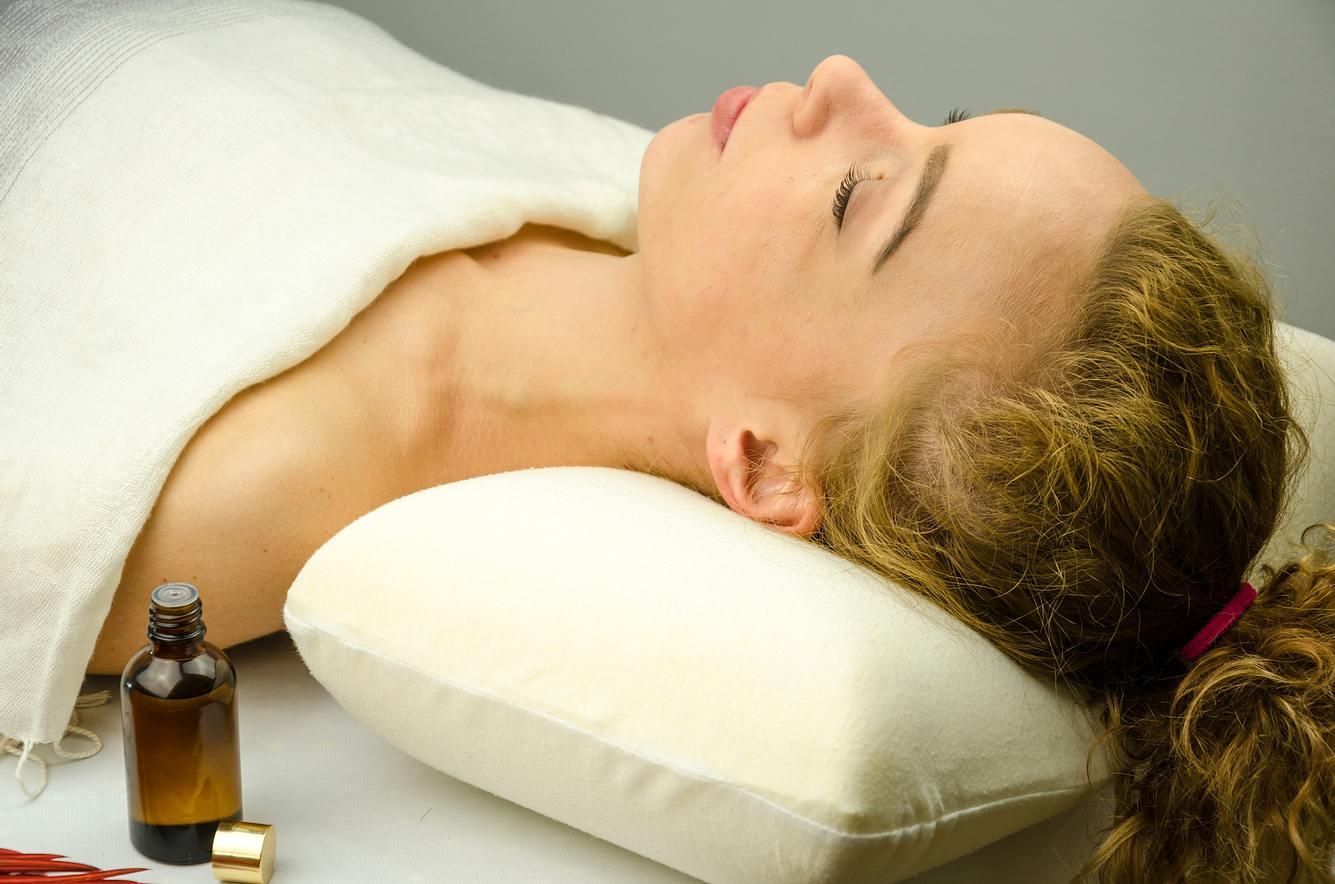 Frau auf weißem Shiatsu Massagekissen mit geschlossenen Augen