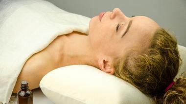 Frau auf weißem Shiatsu Massagekissen mit geschlossenen Augen - Foto: iStock/RobertoDavid